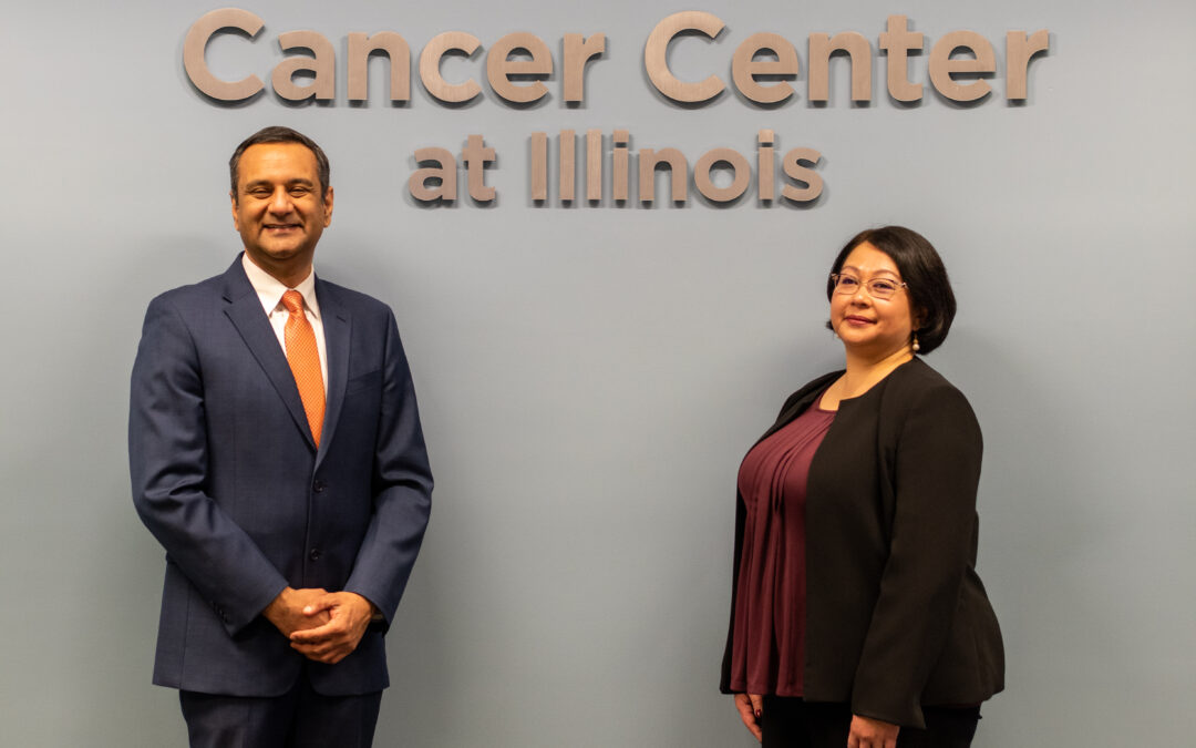 Photo of Rohit Bhargava and Georgina Cheng in front of Cancer Center at Illinois sign
